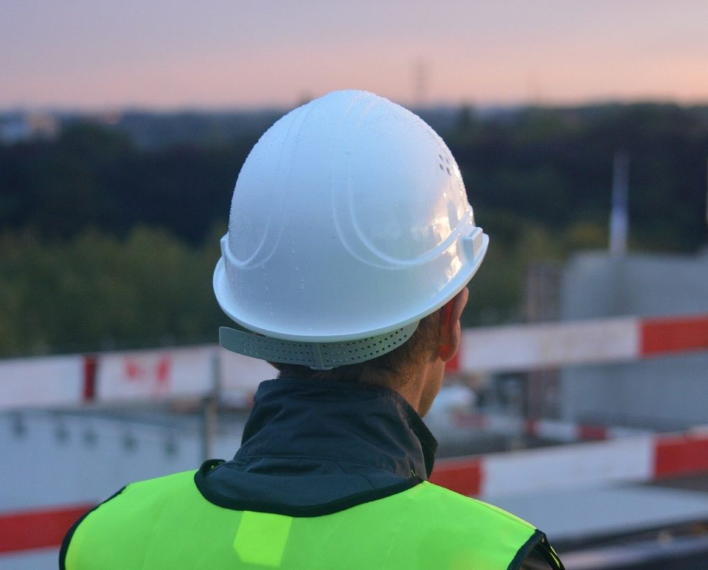 Construction worker in hard hat looks out over site